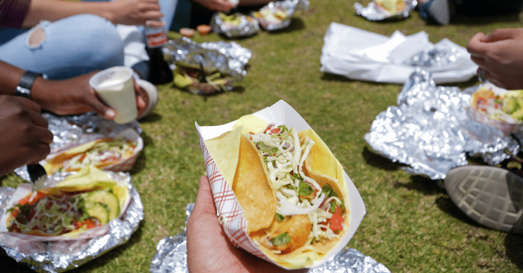 Group of friends enjoying tacos in the park in San Diego
